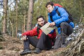 Backpackers with map in forest