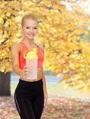 sport, fitness and diet concept - smiling sporty woman with protein shake bottle