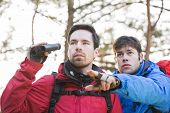 Hiker showing something to friend holding binoculars in forest