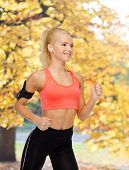 sport, exercise, technology, internet and healthcare - smiling sporty woman running and listening to
