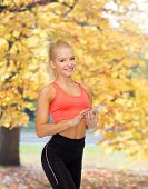 sport, fitness, technology, internet and healthcare concept - smiling sporty woman with smartphone
