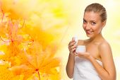 Young healthy girl with body cream on autumnal background