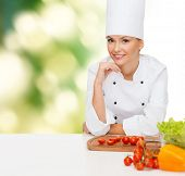 cooking and food concept - smiling female chef with vegetables