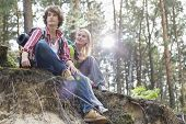 Young hiking couple sitting on edge of cliff in forest