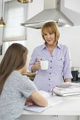 Mother holding coffee cup while looking at girl studying in kitchen