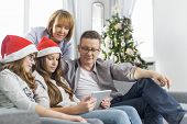 Family of four using digital tablet at home during Christmas