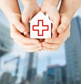 healthcare, medicine and charity concept - male and female hands holding white paper house with red