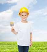 profession, future, childhood and people concept - smiling little boy in protective helmet with pain