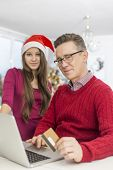 Portrait of father and daughter shopping online during Christmas