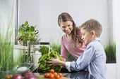 Happy mother looking at son washing vegetables in kitchen