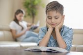 Boy reading book with mother in background at home