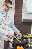 Happy man adding white wine to saucepan while cooking in kitchen