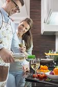 Happy man pouring white wine in glass while cooking with woman at kitchen