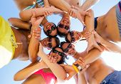 friendship, summer vacation, teamwork and people concept - group of smiling friends wearing swimwear