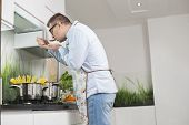 Side view of man tasting food while cooking in kitchen