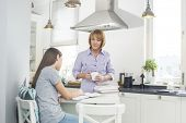 Mother holding coffee cup while looking at daughter studying in kitchen