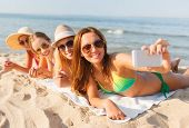 summer vacation, travel, technology and people concept - group of smiling women in sunglasses making selfie with smartphone on beach