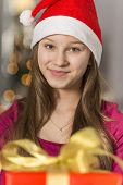Close-up portrait of smiling girl wearing Santa hat