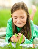 Portrait of a little girl laying on green grass, outdoor shoot