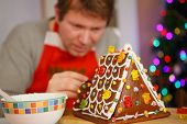 stock photo of gingerbread house  - Young man preparing a gingerbread cookie house for his children at christmas time - JPG