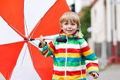 Beautiful Boy With Red Umbrella And Colorful Jacket Outdoors At Rainy Day