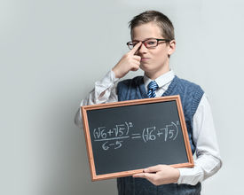 foto of swagger  - The cute smart swagger schoolboy teenager in a glasses shows the black chalkboard with the mathematical equation - JPG