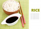 Bowl of rice and chopsticks on bamboo mat with space for your text