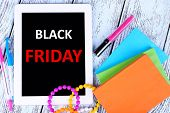 Tablet with Black Friday text on screen, bracelets, notebook and pens on wooden background