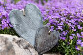 Two Wooden Hearts In Front Of Purple Blossoms
