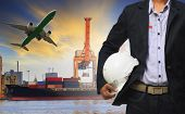 image of ship  - manager man holding safety helmet standing against ship and container on shipping port and cargo plane flying above use for freight and logistic transport industry - JPG