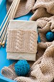 image of blanket snow  - Old notebook with knitted wrap beige knitted blanket and spokes lie on blue background - JPG