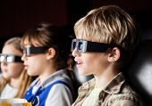 Boy watching 3D movie with siblings in cinema theater