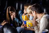 Family showing silence gesture to woman using mobilephone in cinema theater