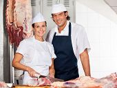 Portrait of confident female butcher cutting meat while standing by male colleague at counter in shop