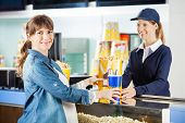 Portrait of smiling pregnant woman buying popcorn and drink from seller at cinema concession counter
