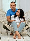 Couple Relaxing In Hammock Smiling, Sitting At Home