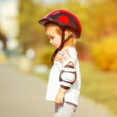 two year old pretty girl in  a helmet on the street close-up