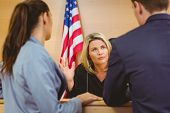 stock photo of court room  - Judge and lawyers speaking in front of the american flag in the court room - JPG