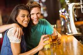 Smiling friends talking and drinking beer and mixed drink in a bar