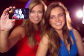 Pretty friends taking a selfie at the nightclub