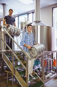 stock photo of keg  - Young men carrying keg smiling at camera in the factory - JPG