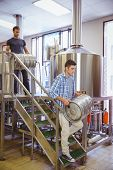 picture of keg  - Young men carrying keg smiling at camera in the factory - JPG