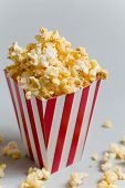 picture of popcorn  - Full popcorn in classic popcorn box on grey background - JPG