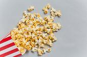image of popcorn  - Full popcorn in classic popcorn box on grey background - JPG