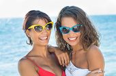 Two Beautiful Smiling Young Women With Sunglasses On Summertime