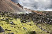 Iceland in July. Rhyolitic mountains smoke underground heat. In hollows last year's snow lie