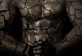 stock photo of drought  - sporty male body with cracks - JPG