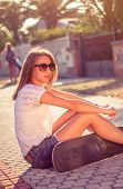 Young girl with skateboard sitting outdoors on summer
