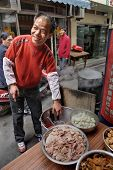 Street Smiling Chef Sells Hot Food On A Narrow Piece.
