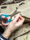 Closeup of woman's hands unraveling fabric border using scissors